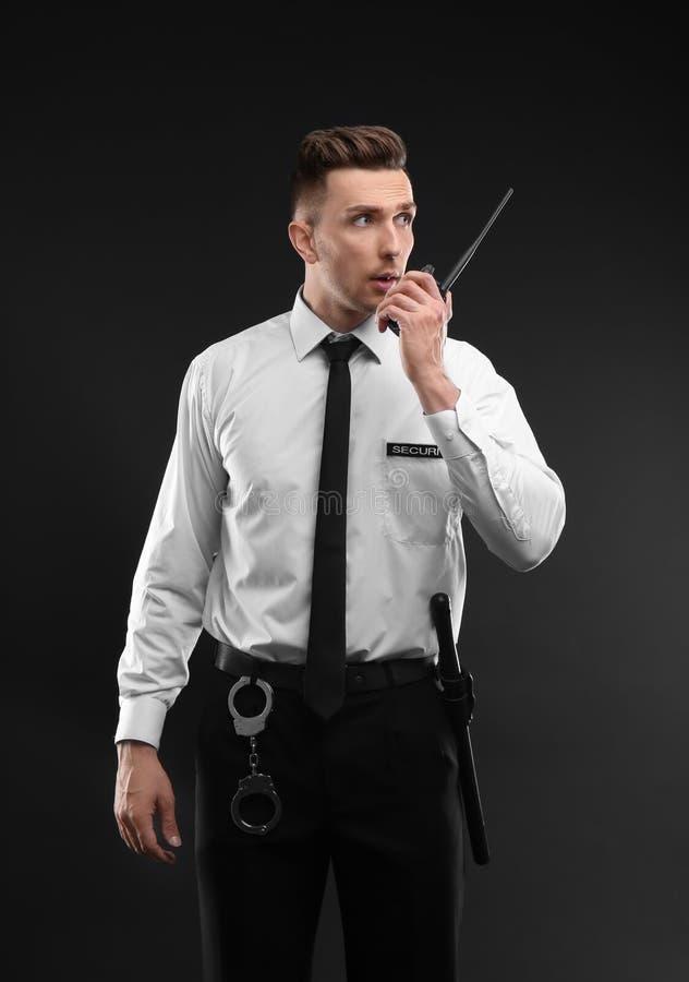 Manlig ordningsvakt som använder sändaren för bärbar radio på mörk bakgrund royaltyfri fotografi