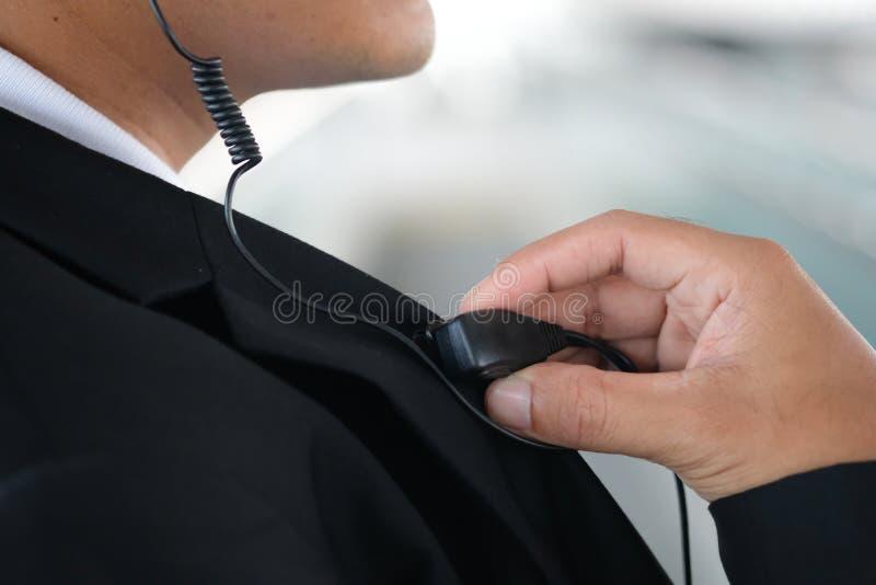 Manlig ordningsvakt som utomhus använder den bärbara radion arkivbild