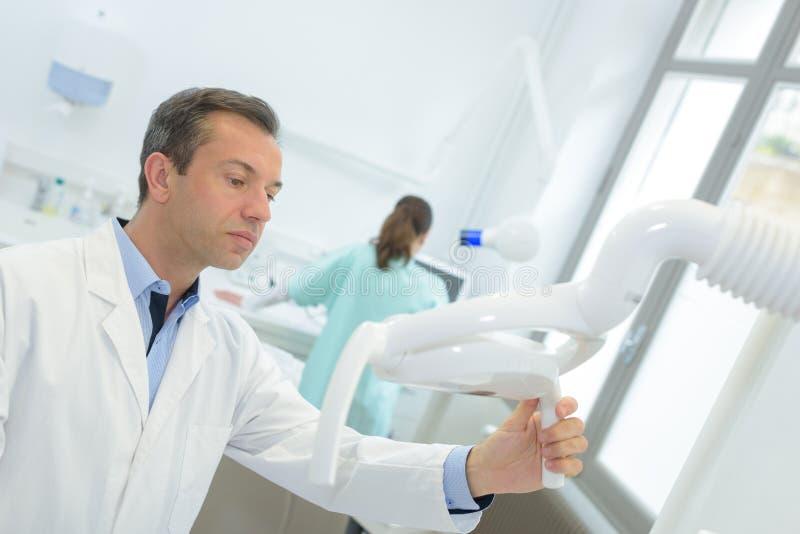 Manlig orthodontist som justerar styrning på det panorama- färgpulvret arkivbild