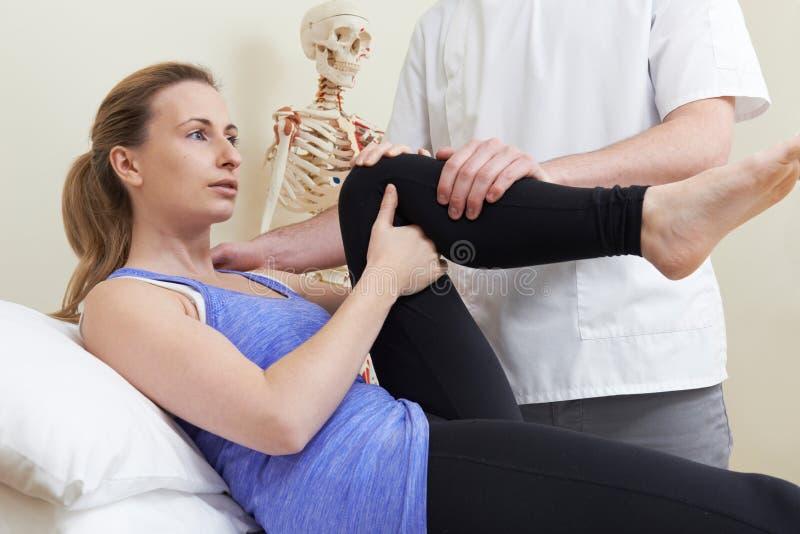 Manlig osteopat som behandlar den kvinnliga patienten med höftproblem arkivbilder