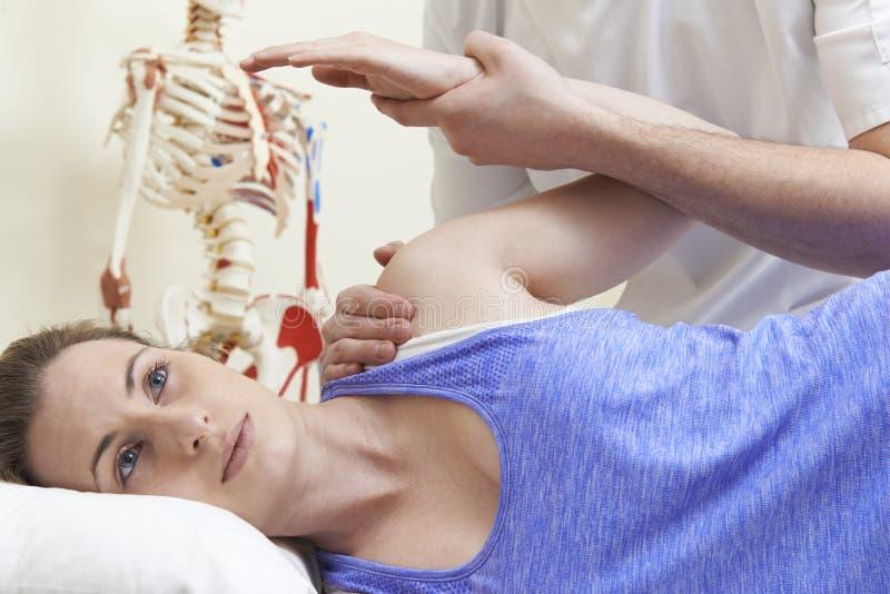Manlig osteopat som behandlar den kvinnliga patienten med skuldraproblem arkivfoton