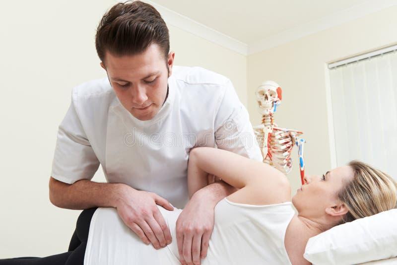 Manlig osteopat som behandlar den kvinnliga patienten med tillbaka problem royaltyfria foton