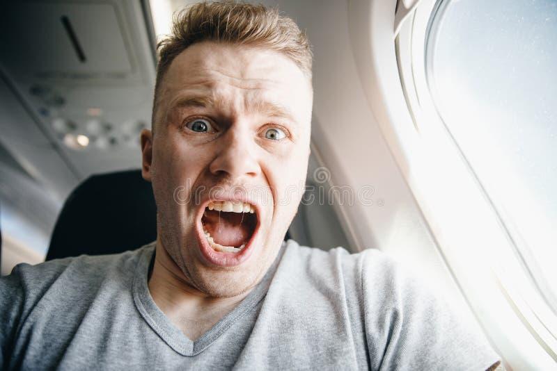 Manlig passagerare i plana skrin och skrik, aerophobia bakgrund av hyttventilen Begreppsskräck av flyget på flygplanet royaltyfri fotografi