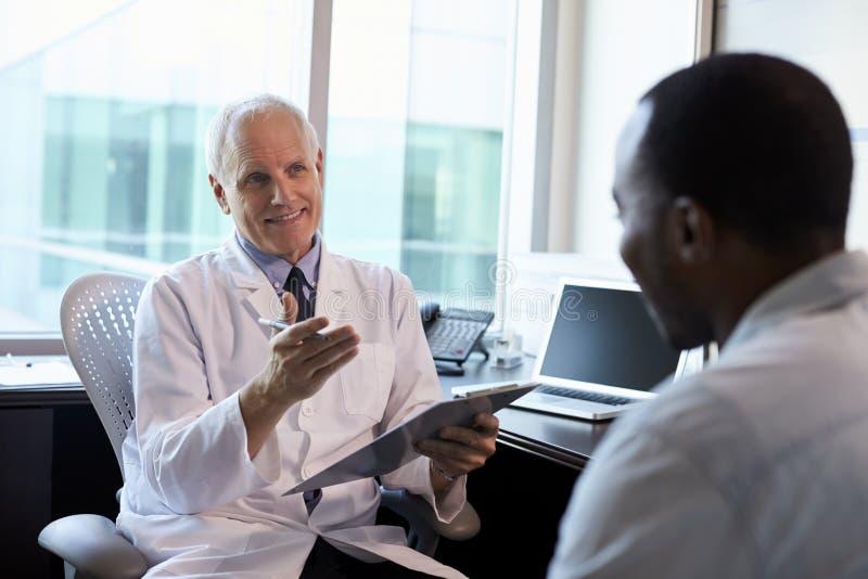 Manlig patient för doktor In Consultation With i regeringsställning fotografering för bildbyråer