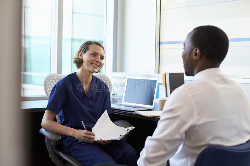 Manlig patient för doktor In Consultation With i regeringsställning royaltyfria foton