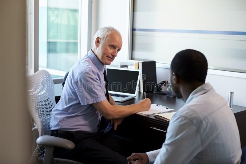 Manlig patient för doktor In Consultation With i regeringsställning arkivfoto