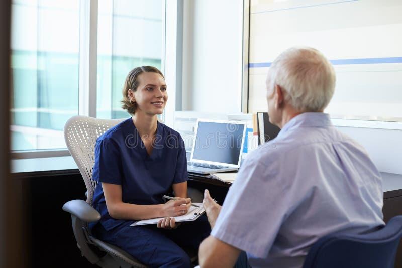 Manlig patient för doktor In Consultation With i regeringsställning arkivfoton