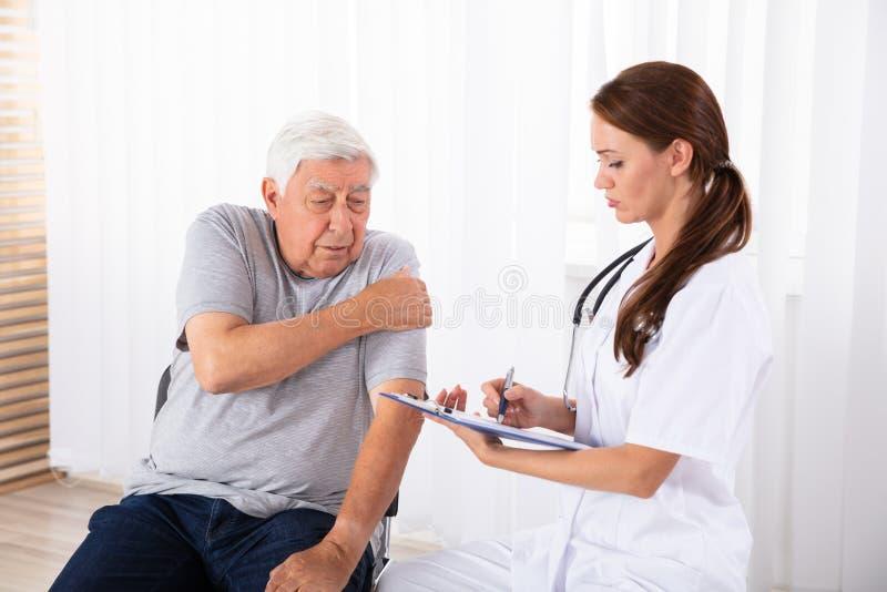 Manlig patient f?r doktor som Giving Prescription To har armen att sm?rta royaltyfri bild