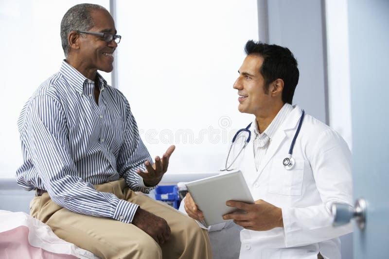 Manlig patient för doktor som In Surgery With använder den Digital minnestavlan arkivbild