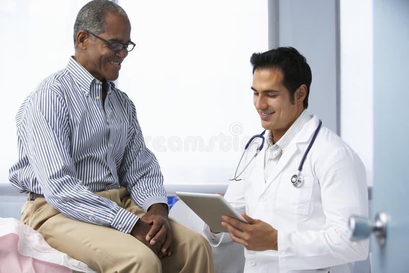 Manlig patient för doktor som In Surgery With använder den Digital minnestavlan royaltyfria bilder