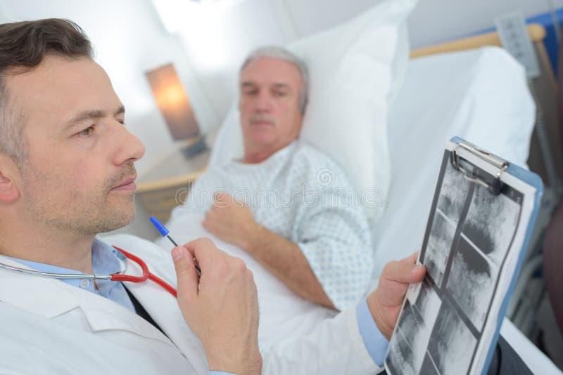 Manlig patient för doktor Talking To Senior i sjukhussäng arkivbilder