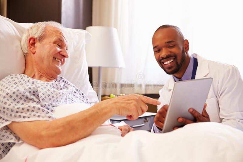 Manlig patient för doktor Talking To Senior i sjukhussäng royaltyfria bilder