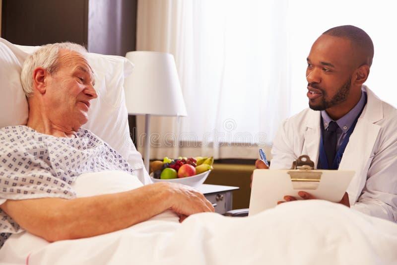 Manlig patient för doktor Talking To Senior i sjukhussäng arkivfoton