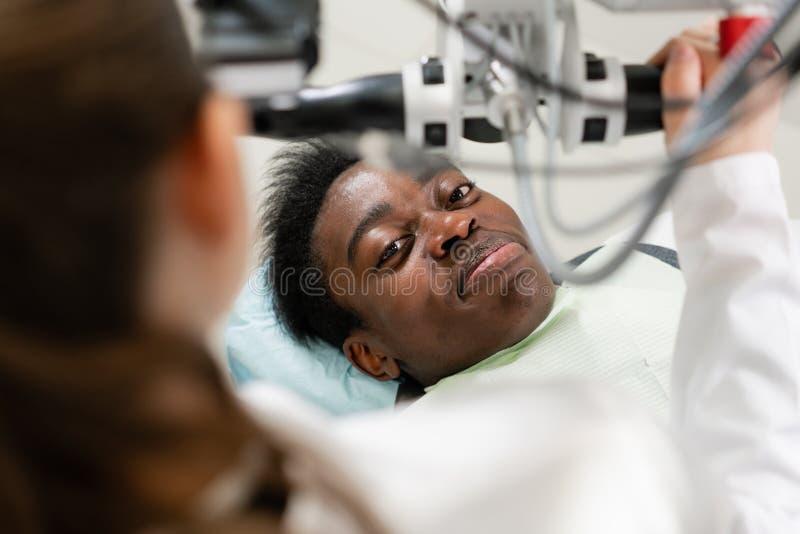 Manlig patient för ung afrikansk amerikan på stol på den tand- kliniken Medicin hälsa, stomatologybegrepp tandläkareuppföranden arkivbild
