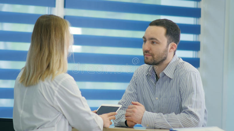Manlig patient med den öm halsen som får doktorstidsbeställning på mottagandet arkivbild