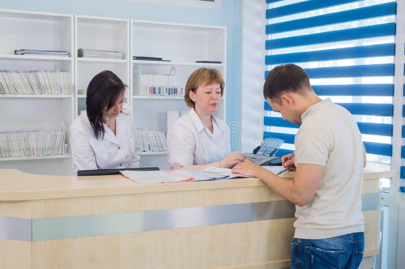 Manlig patient med doktorn och sjuksköterskan på mottagandeskrivbordet i sjukhus royaltyfri fotografi