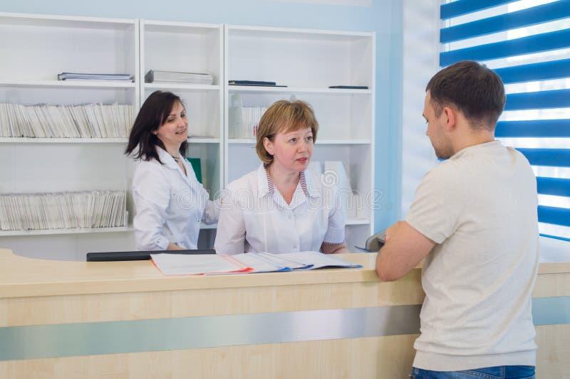 Manlig patient med doktorn och sjuksköterskan på mottagandeskrivbordet i sjukhus arkivfoto