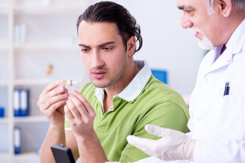 Manlig patient med utfrågningproblem som besöker doktorsotorhinolaryng royaltyfri foto