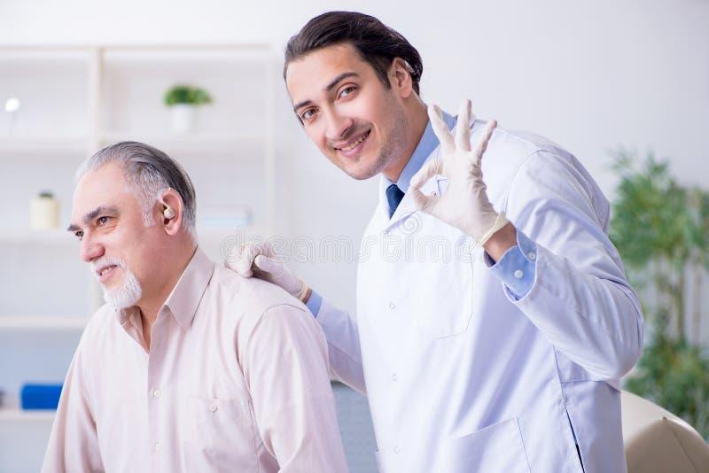 Manlig patient med utfrågningproblem som besöker doktorsotorhinolaryng arkivfoto