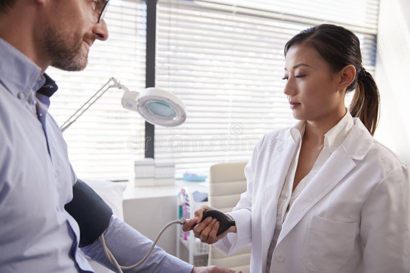 Manlig patient som har blodtryck att tas av kvinnlig doktor In Office royaltyfri fotografi
