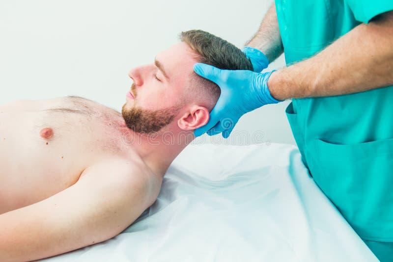 Manlig patient som mottar massage fr?n kiropraktorn f?r terapeut som A str?cker hans patients hals i medicinskt kontor neurologic arkivfoto