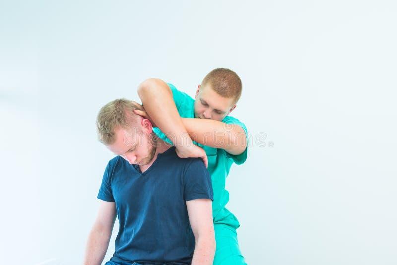 Manlig patient som mottar massage fr?n kiropraktorn f?r terapeut som A str?cker hans patients hals i medicinskt kontor neurologic arkivbilder