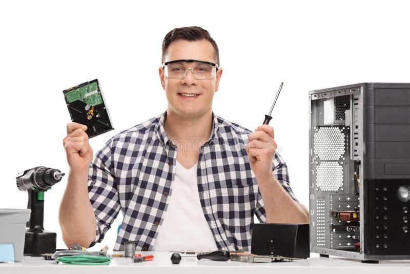 Manlig PCtekniker som rymmer en datordel arkivbild