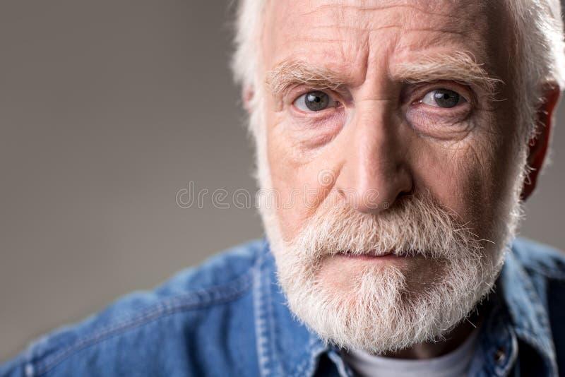 Manlig pensionär som ser med gravitation royaltyfria bilder