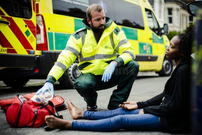 Manlig person med paramedicinsk utbildning som kontrollerar på en sårad kvinna på en väg arkivbild