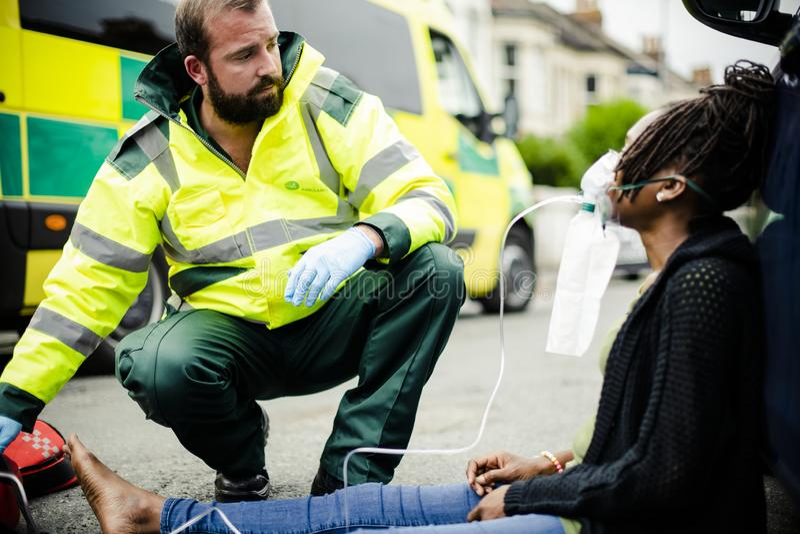 Manlig person med paramedicinsk utbildning som sätter på en syremaskering till en sårad kvinna på en väg royaltyfri bild