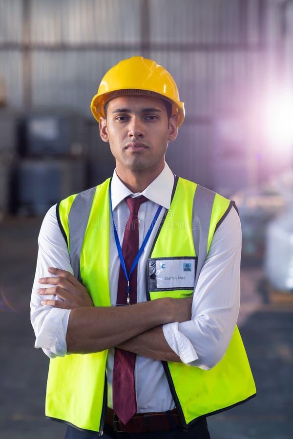 Manlig personal i hardhat och reflekterande omslagsanseende med armar som korsas i lager fotografering för bildbyråer