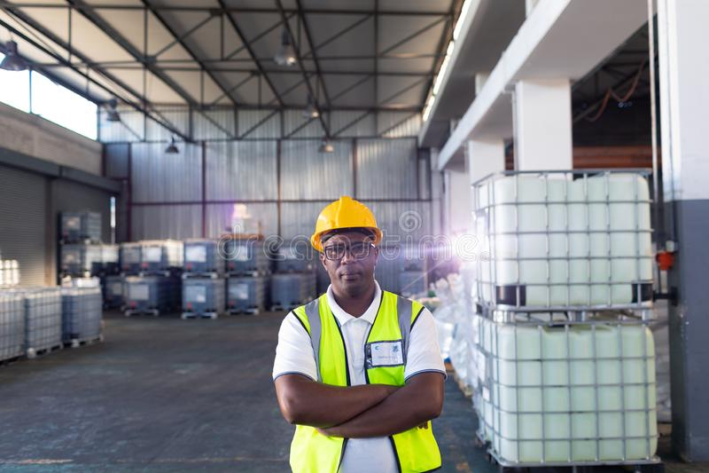 Manlig personal i hardhat och reflekterande omslagsanseende med armar som korsas i lager arkivbilder