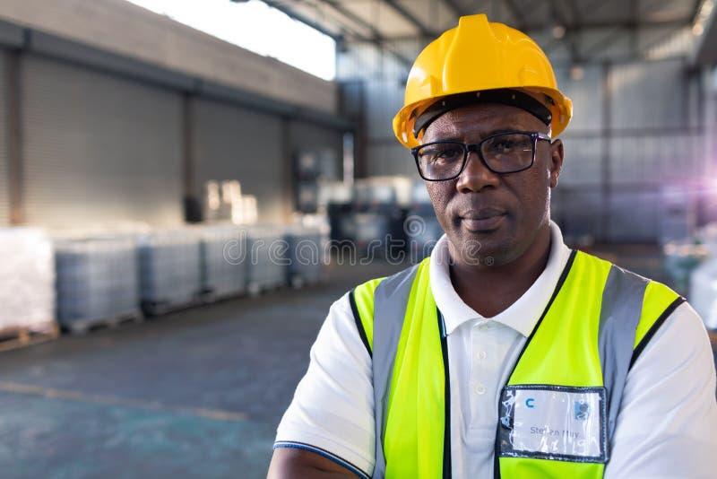 Manlig personal i hardhat och reflekterande omslagsanseende med armar som korsas i lager arkivbild