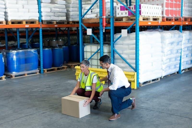 Manlig personal som ger utbildning till den kvinnliga personalen i lager arkivbild