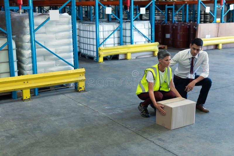 Manlig personal som ger utbildning till den kvinnliga personalen i lager arkivfoto