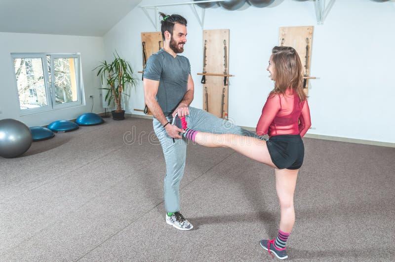 Manlig personlig instruktör för stilig yoga med ett skägg som hjälper den unga konditionflickan att sträcka hennes muskler efter  royaltyfri foto