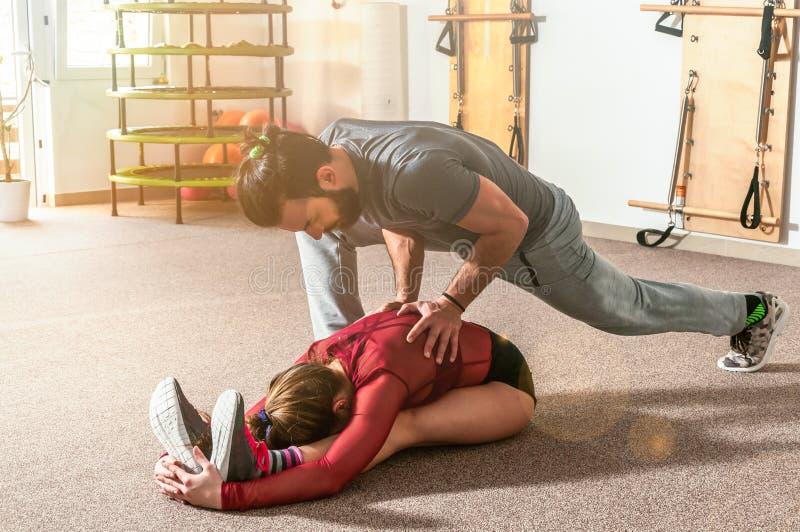 Manlig personlig instruktör för stilig yoga med ett skägg som hjälper den unga konditionflickan att sträcka hennes muskler efter  royaltyfri bild