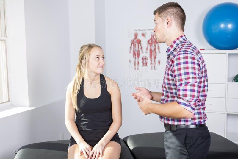 Manlig physio terapeut- och kvinnaportionpatient arkivbilder