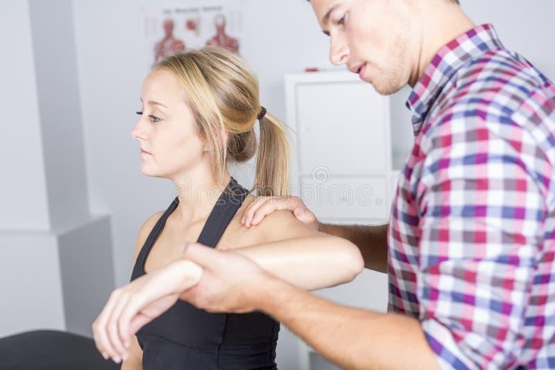 Manlig physio terapeut- och kvinnaportionpatient fotografering för bildbyråer