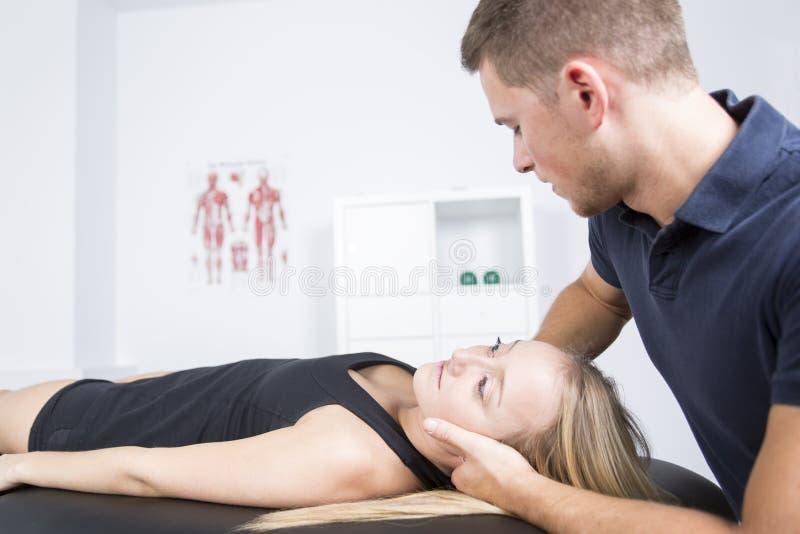 Manlig physio terapeut- och kvinnaportionpatient royaltyfri foto