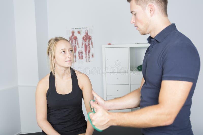 Manlig physio terapeut- och kvinnaportionpatient arkivfoto