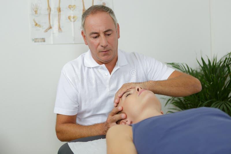 Manlig physio-terapeut som behandlar den kvinnliga patienten arkivfoton