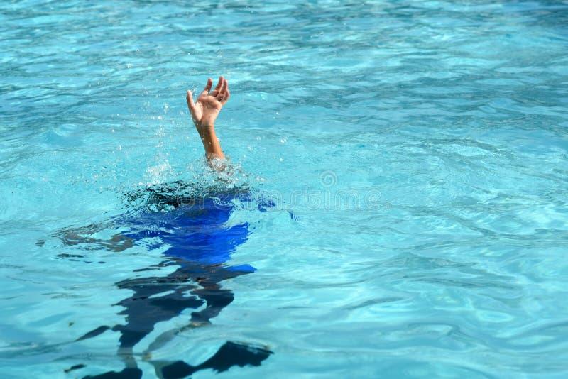 Manlig pojke som kämpar undervattens- drunkning i simbassäng royaltyfri foto