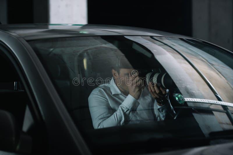 manlig privat kriminalare som gör bevakning vid kameran med objektexponeringsglas från fotografering för bildbyråer