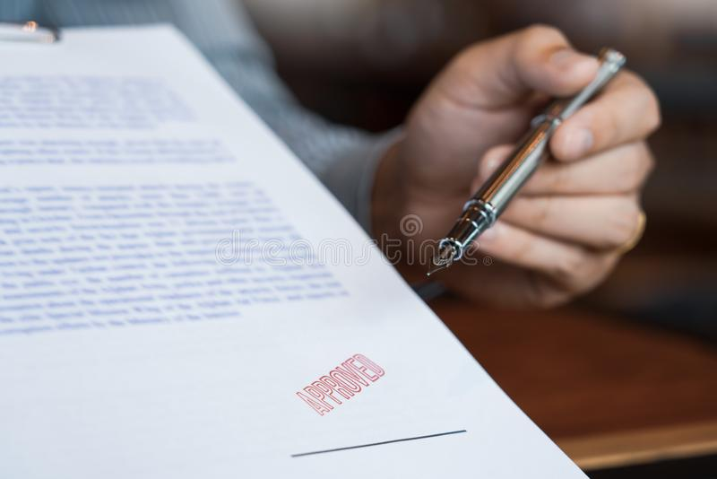 Manlig punkt till det undertecknande affärsdokumentet för att sätta häftet, reservoarpenna och godkänt stämplade på ett dokument, royaltyfri foto