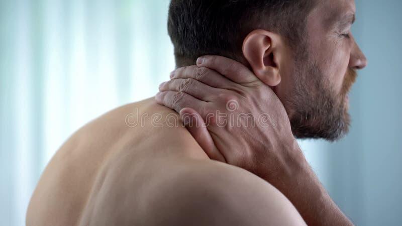 Manlig rörande hals, kännande stark konvulsionupperbaksida, knapert nerv, obehag royaltyfria foton