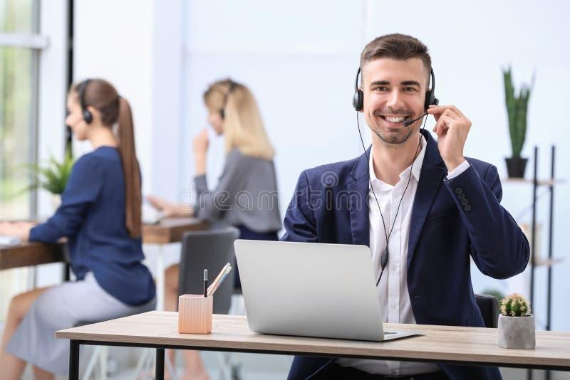 Manlig receptionist med hörlurar med mikrofon på skrivbordet arkivfoton
