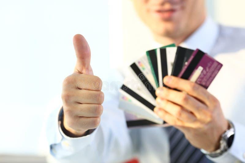 Manlig reko armshow eller att bekräfta att rymma gruppen av kreditkortar royaltyfria foton