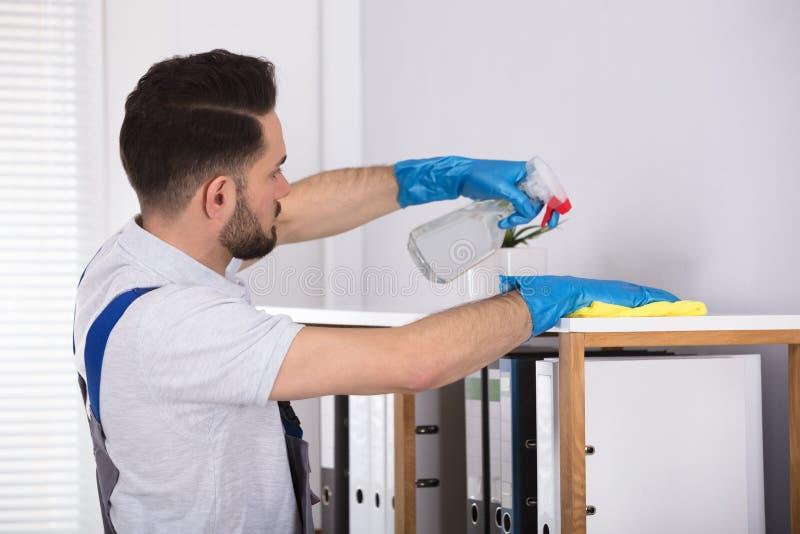 Manlig rengöringsmedellokalvårdhylla på arbetsplatsen arkivbild