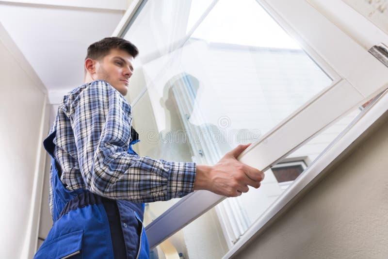 Manlig Repairman Installing Window royaltyfri bild